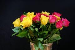 Boeketten van langzaam verdwijnende gele en roze rozen in een glasvaas Royalty-vrije Stock Foto's
