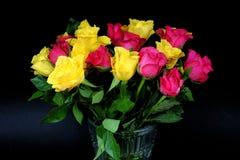 Boeketten van langzaam verdwijnende gele en roze rozen in een glasvaas Stock Foto's