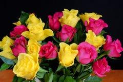 Boeketten van langzaam verdwijnende gele en roze rozen op een houten lijst Royalty-vrije Stock Fotografie
