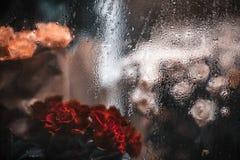 Boeketten van rode, witte en gele rozen achter venster met regen Stock Foto's