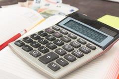 Boekhouding en bedrijfseconomiebankbiljetten, calculator en Euro bankbiljetten op houten achtergrond Belasting, debet en kostprij Royalty-vrije Stock Fotografie
