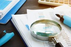 Boekhouding en controle Vergrootglas en bedrijfsdocumenten stock afbeeldingen