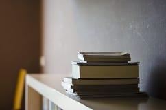 Boekstapel op een plank met schaduwverlichting Royalty-vrije Stock Foto's