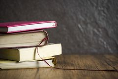 Boekstapel op houten lijst met donkere zwarte achtergrond/boeken in het concept van het bibliotheekonderwijs royalty-vrije stock foto's