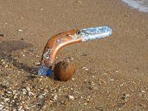 Boemerang en kokosnoot op een strand. Stock Foto