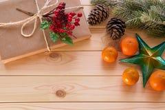 Bożenarodzeniowa dekoracja - gra główna rolę, jedlinowa gałąź, prezent i mandarynki, Fotografia Stock