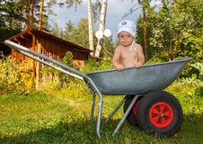 Boerbaby in landbouwbedrijfkruiwagen Stock Afbeelding