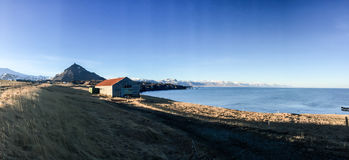 Boerderij, kust, berg, blauwe hemel, Arnarstapi, IJsland Royalty-vrije Stock Afbeelding