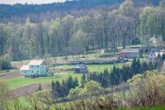 Boerenerf op een heuvel door het bos stock foto's