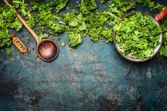 Boerenkool in het koken van pot met houten lepel op rustieke achtergrond, hoogste mening, grens stock foto