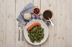 Boerenkool with smoked sausage on a white plate. Boerenkool with smoked sausage, bacon and gravy on a white plate Stock Image