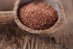 Boete geraspte chocolade in oude houten lepel Royalty-vrije Stock Foto