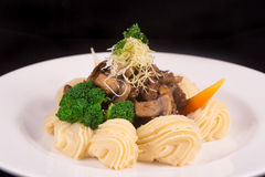 Boeuf Bourguignon topped with parmesan cheese, broccoli, parsley, carrot, and creamy mashed potato. On black background Royalty Free Stock Photo