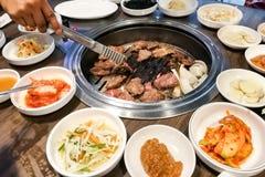 Boeuf de barbecue de personne sur le puits de BBQ pendant l'ensemble coréen de repas photos stock