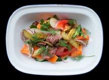 Boeuf et légumes de rôti dans le plat d'émail d'isolement sur le noir Image libre de droits