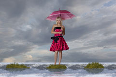 Bog. The girl with an umbrella costs on a bog stock image