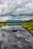 Bog and mountains showing as reflections on a small calm bog Stock Image