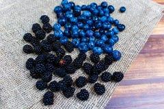 Bog whortleberries and blackberries macro. Ripe berries on linen cloth macro royalty free stock photos