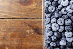 Bog whortleberry place for text. Ripe organic bog whortleberry in a plastic container on a wooden background Stock Photo
