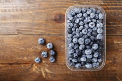Bog whortleberry place for text. Ripe organic bog whortleberry in a plastic container on a wooden background Stock Image