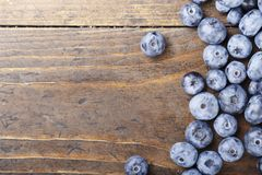 Bog whortleberry scattered on wooden background. Top view Royalty Free Stock Photo