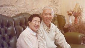 Bogaci Azjatyccy starsi rodzice siedzą w luksusowym pięknym domowym backgrou obrazy stock