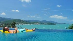 Bogaty człowiek relaksuje na żółtej materac w przejrzystym wodnym nieskończoność basenie zdjęcie wideo