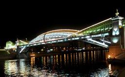 Bogdan Khmelnytsky Bridge (den Kiev fotbron) till och med den Moskva floden i Moskva på natten. Arkivfoto