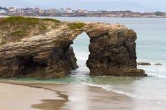 Bogen auf dem Strand der Kathedralen und der Stadt von Foz stockfotografie