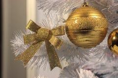 Bogen und Ball für Dekoration der Goldfarbe mit Pailletten auf einem Baum der weißen Weihnacht Weihnachtsvorbereitungen, Innenein stockfotografie