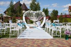 Bogen und Stühle an der Hochzeitszeremonie Stockfotografie