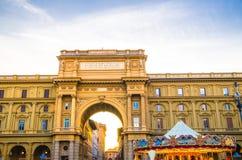 Bogen zwischen Gebäuden und Weinlesekarussell auf Marktplatz della Repubblica-Republikquadrat in der historischen Mitte von Flore lizenzfreie stockbilder