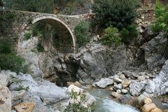 Bogenbrücke über einem Gebirgsfluß Stockfotos