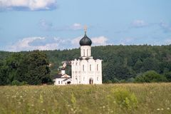 View through Bogolubovo meadow towards the Church of the Intercession of the Holy Virgin on the Nerl River. Bogolyubovo meadow has rich and variety floristic Royalty Free Stock Image