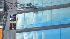 Bogota, Cundinamarca/Colombie - 8 avril 2016 : Travailleurs nettoyant les vitraux d'un bâtiment moderne avec le ciel de réflexion Photos stock