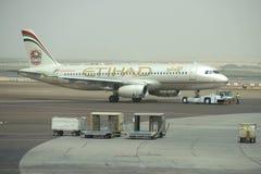 Bogsera flygplanflygbussen A320-232 (A6-EIR) Etihad Airways i passagerarterminalen Abu Dhabi Airport Royaltyfria Foton