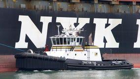 Bogserbåt ROBERT FRANCO av portsidan av NYK-APHRODITEN royaltyfri foto