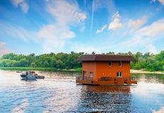 Bogserbåt som bogserar huset vid floden, Dnieper, Kiev, Ukraina royaltyfri bild