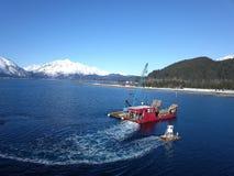 Bogserbåt som eskorterar det alaskabo arbetsfartyget in i hamn royaltyfria foton