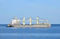 Bogserbåt som hjälper det bulk lastfartyg Royaltyfria Bilder