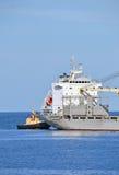 Bogserbåt som hjälper det bulk lastfartyg Arkivfoton