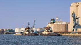 Bogserbåtar förtöjde på ett oljeraffinaderi på ett soligt, port av Antwerp, Belgien arkivbilder