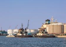 Bogserbåtar förtöjde på ett oljeraffinaderi på ett soligt, port av Antwerp, Belgien royaltyfri foto