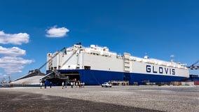 Bogserbåtar knuffar lastfartyget GLOVIS på port av Burgas Arkivbild