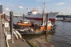 Bogserbåtar och ett lastfartyg arkivfoto