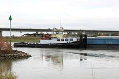 Bogserbåten drar den rudderless fraktbåten på den holländska floden Royaltyfri Fotografi