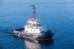Bogserbåtfartyg som är kommande på havsvatten Arkivbild