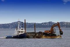Bogserbåtfartyg som skjuter den muddra pråmen Arkivfoto