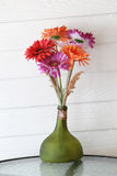 Bogus flowers in the bottle on coffee table. Royalty Free Stock Photos