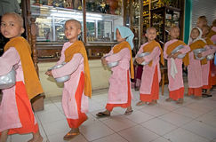 Bogyoke Aung San Market, Yangon, Myanmar. Young females monastic in Buddhism in traditional robes are making alms in the Bogyoke Aung San Market, Yangon, Myanmar Royalty Free Stock Photo